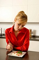 Young woman leaning against a kitchen counter and holding a fork