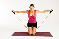 Portrait of a young woman exercising with a resistance band (thumbnail)