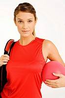 Portrait of a young woman carrying a gym bag and a ball