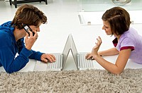Teenage boy and a young woman using laptops