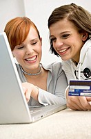 Close_up of two young women holding a credit card and using a laptop