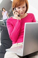 Close_up of a young woman using a laptop and talking on a mobile phone