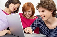 Close_up of two young women and a teenage boy looking at a laptop