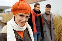 Close_up of a young woman smiling with her friends standing in the background