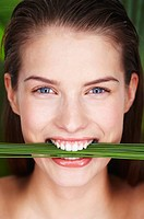 Young smiling woman holding plants between teeth