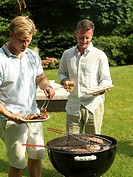 Two men preparing fish on barbeque grill in garden