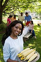 Smiling woman with plate of corn at picnic