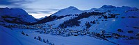 Aerial view of village on snow_covered landscape lit up at night, Arlberg, Austria