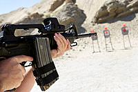 Man aiming machine gun at firing range close up of hands