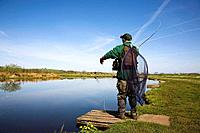 Man fishing for trout using rod and line