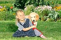 girl and young Golden Retriever in the garden