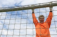 Cheering goalkeeper hanging on goal