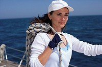 Woman on a boat carrying a rope on her shoulder