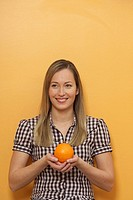 A woman is holding an orange in her hands