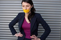 Yellow adhesive tape over businesswoman's mouth