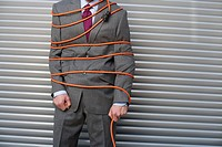Businessman tied up with power cord