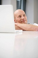 Mature man crouching at a table with a laptop