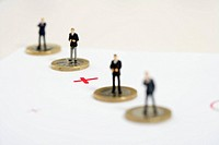 Plus sign between businessmen figurines standing on one Euro coins