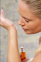 Young woman smelling perfume on hand