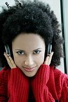 Young African American woman listening to headphones at airport.