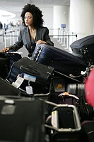 African American businesswoman looking for luggage in airport.