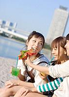 Women eating hotdog at the seaside