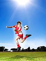 Young boy in uniform kicking soccer ball