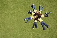 Group of children laying on grass in circle formation