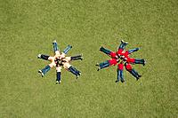Two groups of children laying in a circle formation