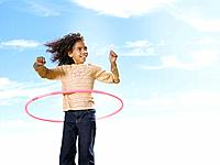 Young girl playing with hula hoop