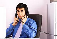 Businessman talking on two telephones at one time