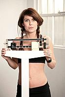 Young woman using weight scale