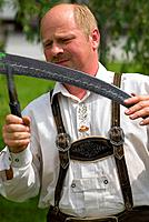 Man in leather trouser sharpening scythe, Reichraming, Upper Austria, Austria