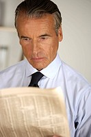 Senior businessman reading a newspaper