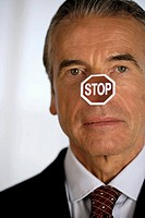 Senior businessman with a STOP label on his nose
