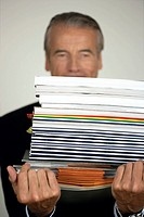 Senior businessman carrying a stack of documents