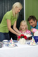 Little blond girl blowing out the candles of her birthday cake