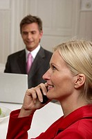 Young blond woman is phoning in front of a man who is working with a laptop, selective focus