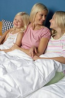 Mother sitting in bed between her two blond daughters, close_up