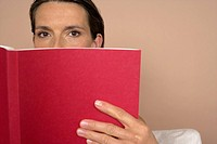 Woman looking over a red book