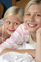 Two blond girls lying smiling in bed, close_up