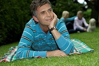 Man lying on a blanket in front of his family in a park, selective focus