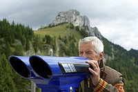 Senior adult man is looking through binoculars in the mountains, selective focus