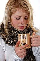 Young woman with cold holding cup of tea, scarf