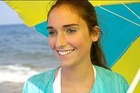 Young brunette woman under an umbrella at the beach, close_up
