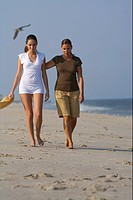 Two young women walking along the beach, selective focus