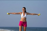 Young brunette woman training with tiny barbells at the beach