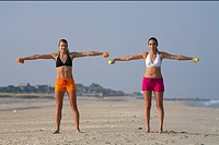 Two young women training with tiny barbells at the beach