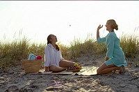 Blond woman throwing a grape to her friend, both at the beach