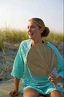Young blond woman with a fan in her hand sitting at the beach, close_up